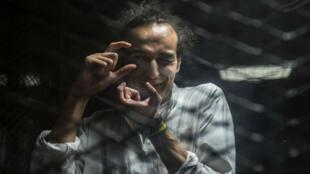 """Mahmoud Abu Zeid, alias """"Shawkan"""", feint de prendre une photo, lors d'une audience au Caire, le 9 août 2016."""