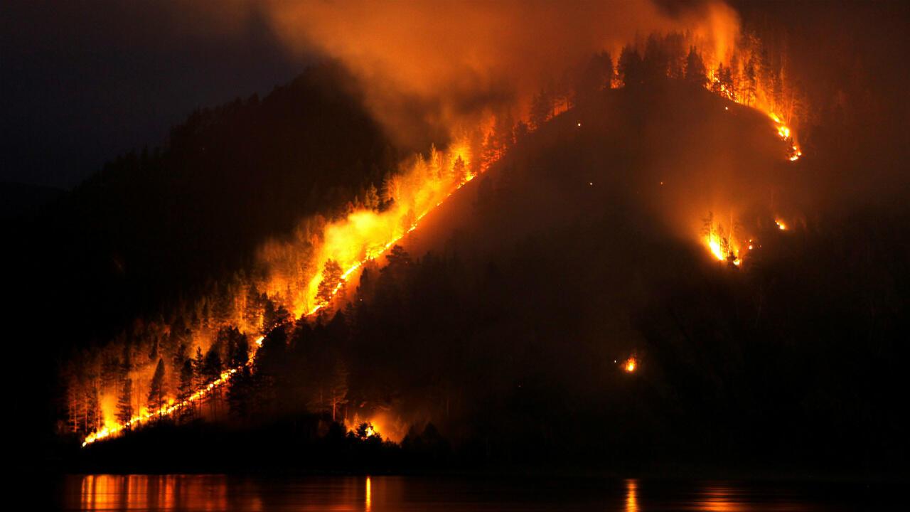 Les arbustes et les arbres brûlent sur la rive de la rivière Yenisei dans le district de Taiga, en Sibérie, le 12 juillet 2019.