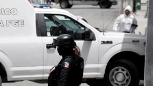 Un policía federal y un miembro de un equipo forense son vistos en la escena de un crimen donde un hombre fue asesinado a tiros por desconocidos en Cancún, México el 29 de julio de 2018.