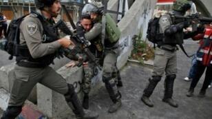 جنود إسرائيليون يعتقلون فلسطينيا خلال مواجهات شمال رام الله بالضفة الغربية المحتلة في 22 ديسمبر 2017