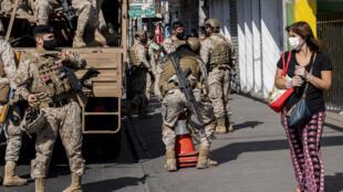 Una mujer usa máscara facial como medida de precaución contra la propagación del nuevo coronavirus, COVID-19, mientras camina junto a un camión de soldados en Santiago, Chile, el 17 de abril de 2020.