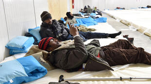 Philippe Huguen, AFP   Migrants lie on mattresses placed on the floor of a warehouse in Calais, northern France, on December 27, 2014