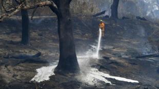 A firefighter sprays water after a fire impacted Clovemont Way, Bundoora in Melbourne, Australia, Dec. 30, 2019.