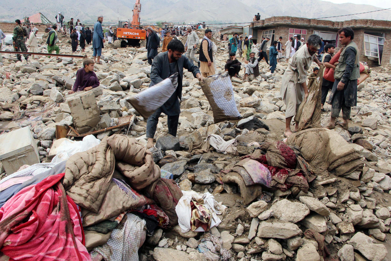 Des Afghans recherchent leurs affaires emportées dans un crue à Charikar, en Afghanistan, le 26 août 2020.
