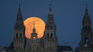 Sobre la Catedral de Santiago de Compostela, en España, se levanta la luna aún enrojecida por ser primera hora de la noche.