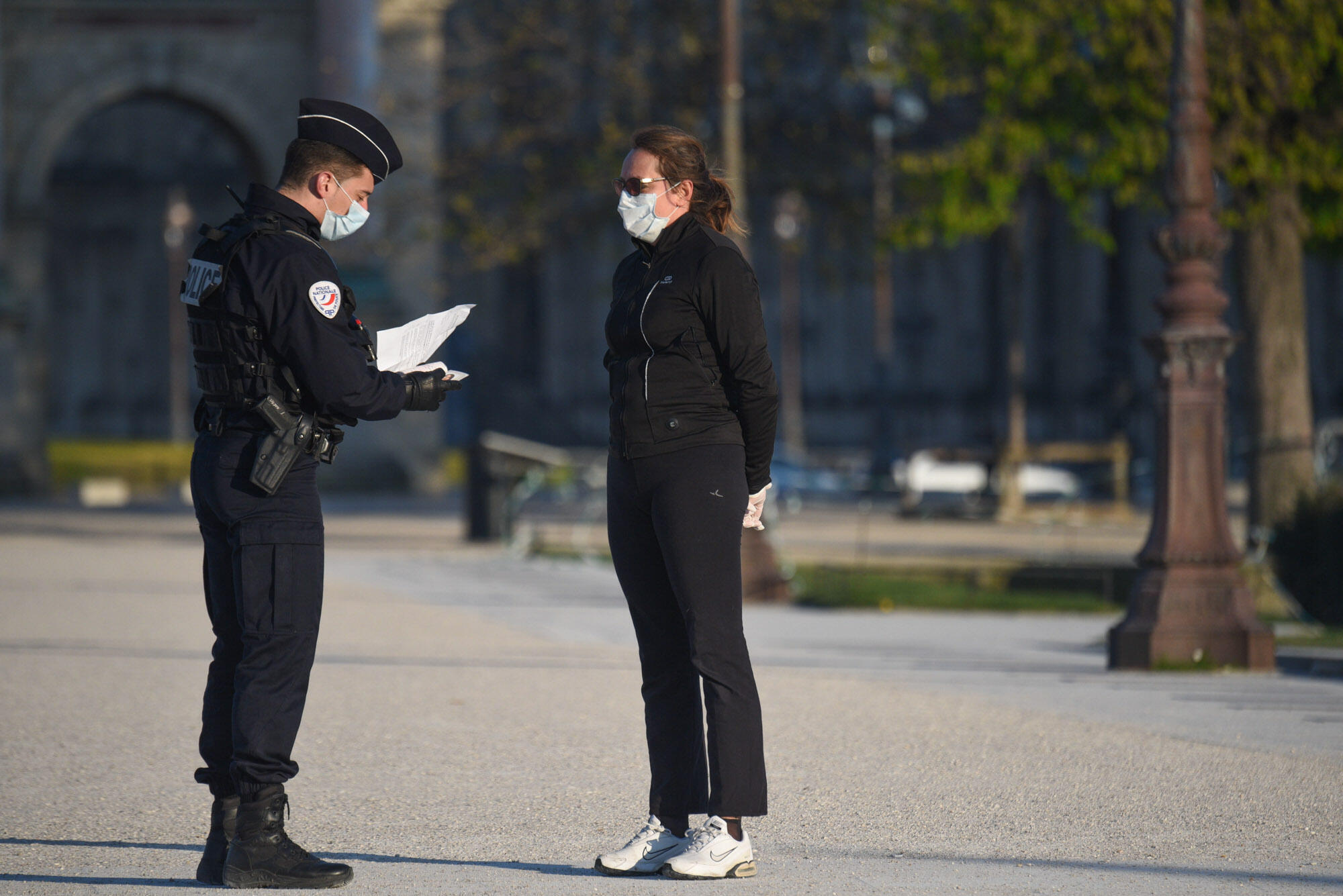 A police officer checks the permission form of a jogger near the Louvre; both wear protective masks. France's scientific council has said the lockdown is currently the only efficient strategy for minimising the spread of the virus. Many expect it to be extended beyond April 15.