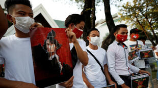 Myanmar citizens hold up a picture of leader Aung San Suu Kyi after the military seized power in a coup in Myanmar, outside United Nations venue in Bangkok, Thailand February 2, 2021.