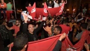 تونسيون في جادة الحبيب بورقيبة بالعاصمة تونس الأحد ليلا إثر إعلان فوز قيس سعيّد
