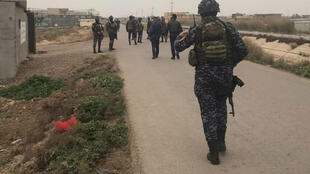 Iraqi forces walk near a building where they found unused Katyusha rockets in Umm al-Izam in this picture provided by Iraqi Media Security Cell on March 14, 2020.