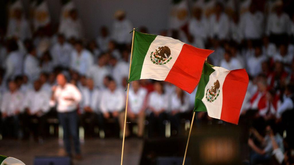 Simpatizantes del candidato a la Presidencia de México, el oficialista José Antonio Meade (fondo-sin foco), agitan banderas nacionales durante su último acto de campaña con simpatizantes de Coahuila el miércoles 27 de junio de 2018, en Saltillo (México).