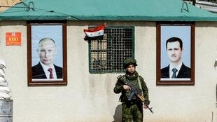 This file photo taken on March 1, 2018 shows a member of the Russian military police standing guard between the portraits of Syrian President Bashar al-Assad, right, and Russian President Vladimir Putin, hanging outside a guard-post at the Wafideen checkpoint on the outskirts of Damascus.