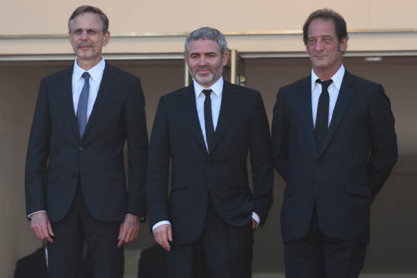 "Vincent Lindon (right), Stéphane Brizé and producer Christophe Rossignon (left) walk the red carpet at Monday's premiere of ""The Measure of a Man""."