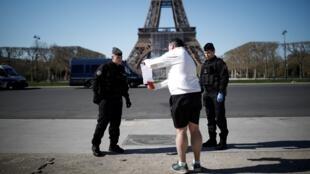 عناصر من الدرك الفرنسي قرب برج إيفل بباريس يراقبون إجراءات الحجر الصحي لوقف انتشار فيروس كورونا، 23 مارس/آذار 2020.