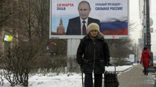 Une femme passant à Saint-Pétersbourg, en janvier dernier, devant un panneau appelant à réélire Vladimir Poutine.