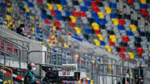 مصور يضع كمامة واقية خلال مباراة فورتونا دوسلدورف وبادربون ضمن الدوري الألماني لكرة القدم، في 16 أيار/مايو 2020.