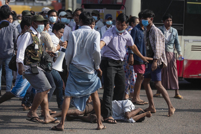 Simpatizantes pro-militares, entre ellos uno blandiendo un cuchillo, se paran sobre un residente después de atacarlo durante una manifestación en Rangún el 25 de febrero de 2021, tras semanas de manifestaciones masivas contra el golpe militar.