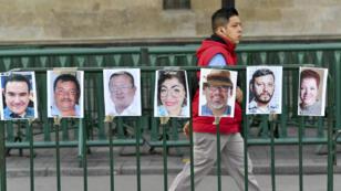 Un homme passant, le 1er juin 2018, à Mexico, devant des portraits de journalistes mexicains assassinés.