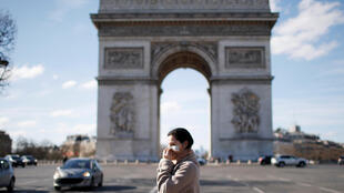 File photo of a woman wearing a protective mask, walks near Arc de Triomphe in Paris.