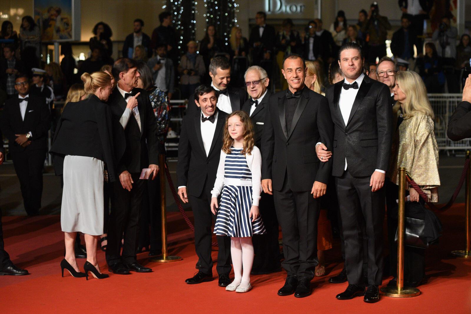 El director italiano Matteo Garrone se prepara para subir los escalones con sus actores antes de la proyección de su película 'Dogman'.