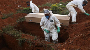Gravediggers wearing protective suits prepare to bury the coffin of a person who died from Covid-19 during a ceremony with no relatives at Vila Formosa cemetery, Brazil's biggest cemetery, in Sao Paulo, Brazil on May 22, 2020.