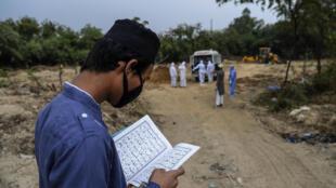 Un allegado de una víctima de coronavirus lee el Corán antes del entierro el 10 de mayo de 2020 en Nueva Delhi