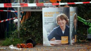 Des fleurs déposées à proximité d'une affiche de campagne de la candidate Henriette Reker, poignardée à Cologne le 17 octobre 2015.