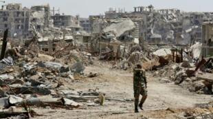 جندي سوري يسير في حي جوبر المدمر في الغوطة الشرقية قرب دمشق في 2 نيسان/أبريل 2018