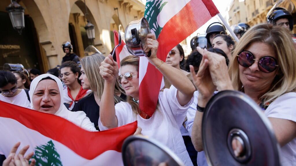 Los manifestantes golpean ollas y cantan consignas frente a los oficiales de policía durante las protestas contra la sesión del Legislativo, en Beirut, 19 de noviembre del 2019.