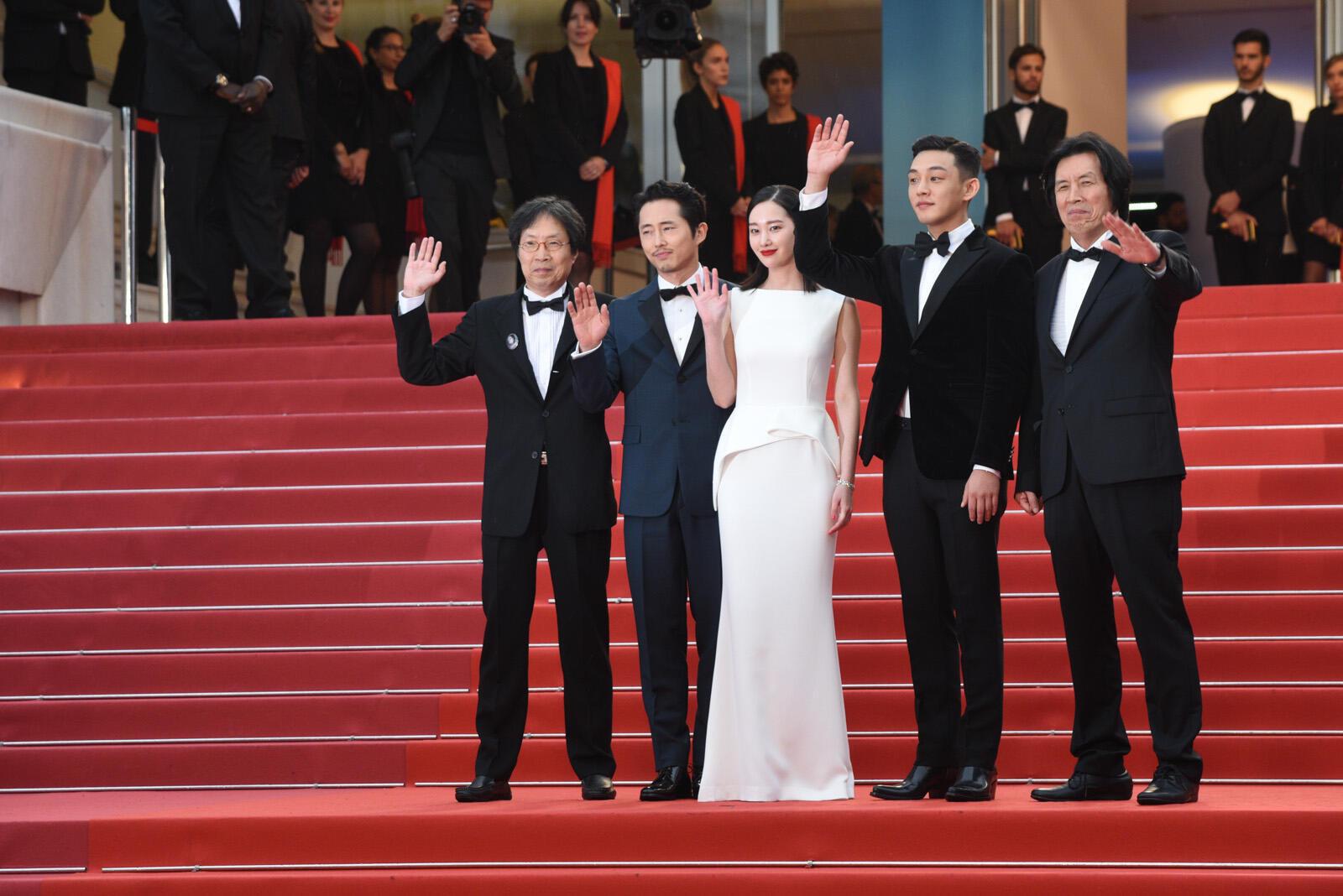 El director surcoreano Lee Chang-Dong, a la derecha y su equipo posan arriba de los escalones antes de la proyección de 'Burning'.