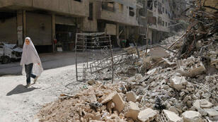 فتاة سورية تمر أمام أنقاض مبنى في أحد شوارع عين ترما بالغوطة الشرقية 19 تموز/يوليو 2017