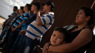 Una mujer inmigrante sostiene a su hijo junto al muro fronterizo mientras ella y otros esperan ser aprehendidos luego de cruzar ilegalmente a los EE. UU. Desde México el 29 de agosto de 2018.
