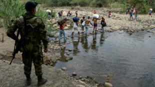 Un soldado colombiano mira a las personas que cruzan por un sendero ilegal a través del río Táchira desde San Antonio, Venezuela, hasta Cúcuta, Colombia, el 27 de febrero de 2019.