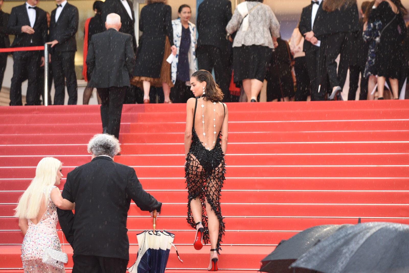 Una mujer sube los escalones del Palacio de los Festivales bajo una lluvia torrencial.