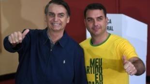 El candidato presidencial de derecha del Partido Social Linberal(PSL) Jair Bolsonaro (I) posa con su hijo y candidato a senador Flavio durante las elecciones generales, en Rio de Janeiro, Brasil, el 7 de octubre de 2018