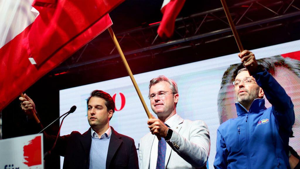 El vicealcalde de Viena, Dominik Nepp, el jefe del Partido de la Libertad, Norbert Hofer, y el ex ministro del Interior, Herbert Kickl, agitan banderas de su país durante un mitin en Viena, Austria, el 27 de septiembre de 2019.