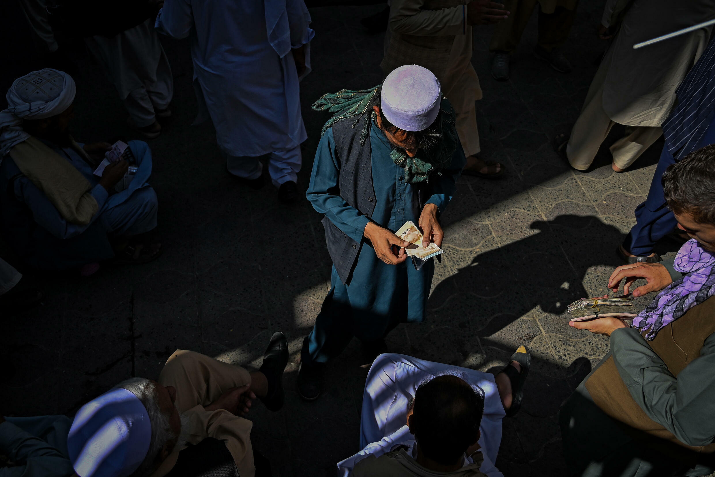 A croupier counts cash at Kabul's main exchange.  The Afghani took a hammer blow since the Taliban returned to power on August 15
