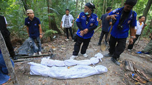 Rescue workers retrieve human remains from graves near the hillside site where shallow graves containing 26 bodies were found on May 1, close to the town of Padang Besar in the southern Thai province of Songkhla on May 13, 2015