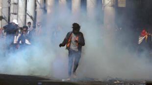 Un manifestant irakien s'échappe du gaz lacrymogène, lors de manifestations antigouvernementales, à Bagdad, le 17 novembre 2019.