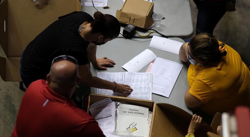 Trabajadores electorales clasifican las boletas de votación en un centro electoral, en San Juan, Puerto Rico, el 16 de agosto de 2020.