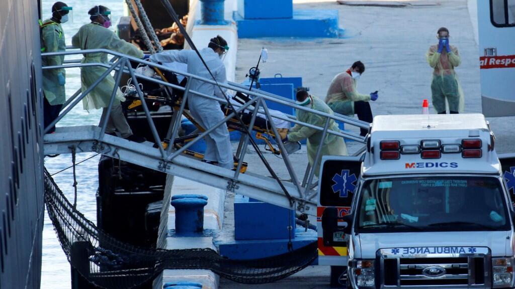 Personal médico realiza el traslado en ambulancia de uno de los pasajeros del Zaandam, tras atracar el Puerto Everglades, en Fort Lauderdale. 2 de abril de 2020.