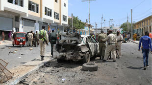 Somali policemen assess the wreckage of a car destroyed at the scene of a bomb explosion in Mogadishu on January 8, 2020.