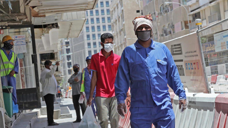 عمال أجانب يضعون كمامات في أحد شوارع العاصمة القطرية