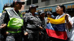 Una enfermera discute con agentes de la policía antidisturbios durante una protesta liderada por los trabajadores del sector de la salud.