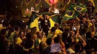 Los partidarios de Jair Bolsonaro, legislador de extrema derecha y candidato presidencial del Partido Liberal Social (PSL), reaccionan en Río de Janeiro, Brasil , el 7 de octubre de 2018.