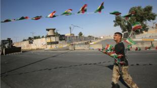 Un militaire irakien détache des drapeaux kurdes à Kirkouk, le lundi 16 octobre.