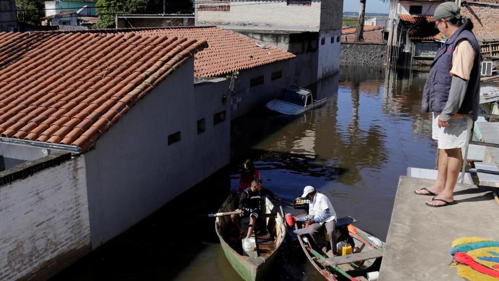 Los residentes son transportados en un bote a través de una calle inundada después de fuertes lluvias que causaron el desbordamiento del río Paraguay , en Asunción, Paraguay, el 25 de mayo de 2019.