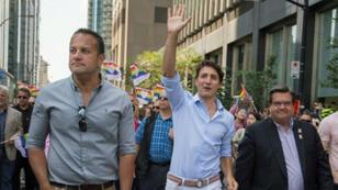 رئيس الوزراء الكندي جاستن ترودو متوسطا نظيره الإيرلندي ليو فارادكار (يسار الصورة) ورئيس بلدية مونتريال دنيس كوديري خلال استعراض لمثليي الجنس في مونتريال في كندا في 20 آب/أغسطس 2017