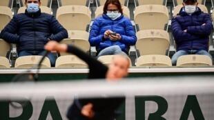 Des spectateurs emmitoufflés et masqués suivent le match entre Anna Karolina Schmiedlova et Venus Williams à Roland Garros, le 27 septembre 2020