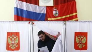 Un votante sale de la urna en la localidad rusa de Khislavichi, 18 de marzo de 2018.