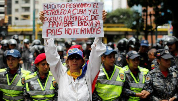 """Una mujer sostiene un cartel que dice: """"Maduro da petróleo a Cuba y la gente muere de hambre. Basta, el país no se da por vencido"""" durante una protesta de los trabajadores del sector de la salud debido a la escasez de medicamentos."""